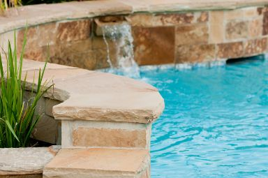 Luxurious-swimming-pool-with-stone-waterfall at townsville pavers
