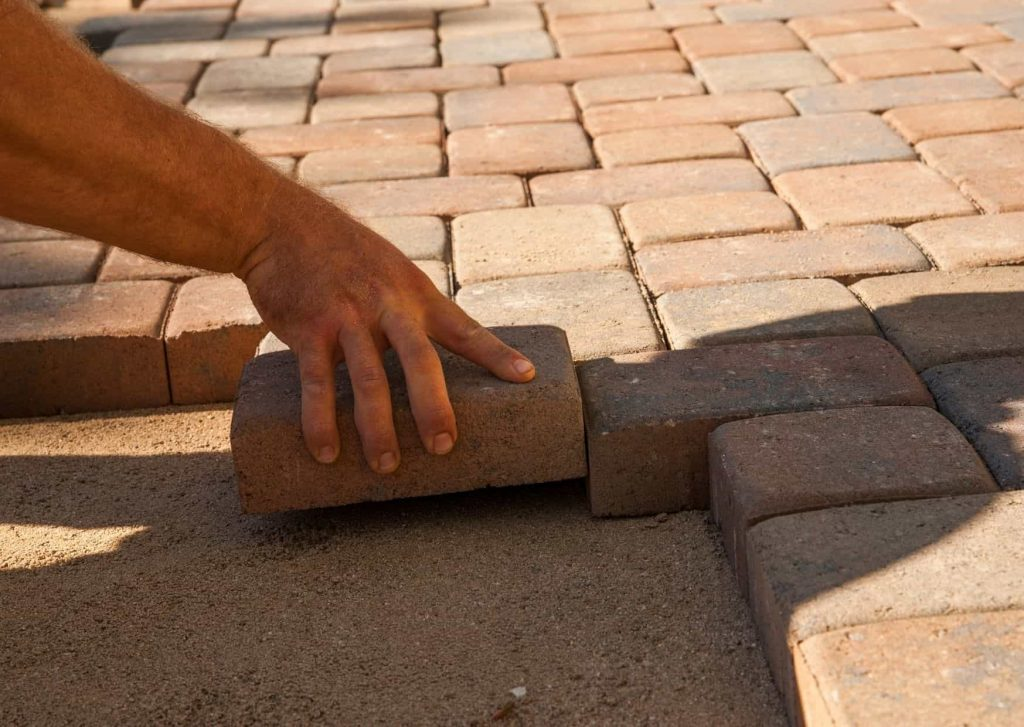 hand laying down bricks at Townsville Pavers